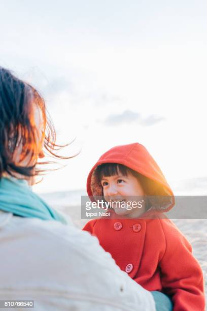 Mother and 3 year old girl having intimate moment on winter beach