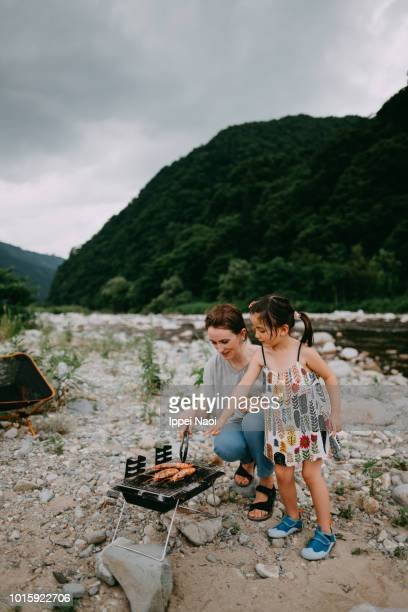 Mother and 4 year old daughter having BBQ by river, Niigata, Japan