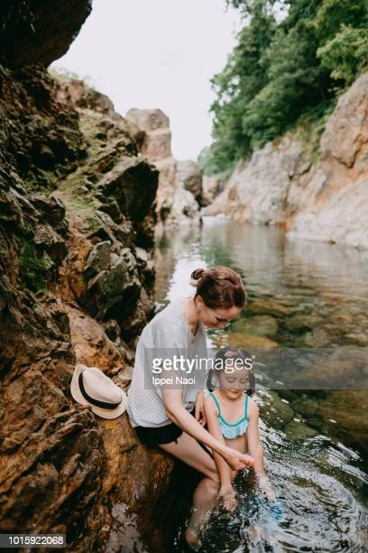 Mother and 4 year old little girl playing in river water, Niigata, Japan