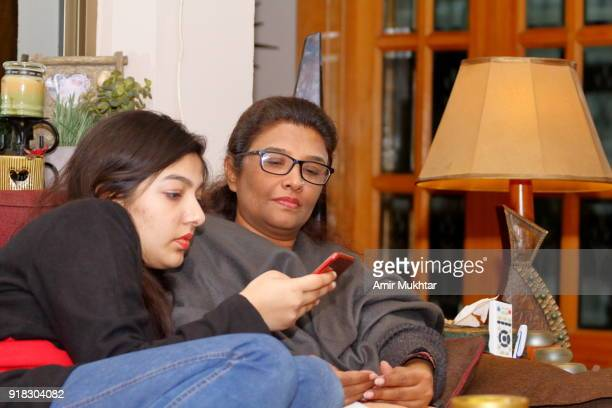 a mother and a daughter watching, sharing and discussing something on cell phone - amir mukhtar stock photos and pictures