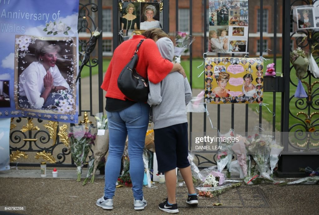 A mother and a son stand in front of floral tributes and photographs left outside one of the entrances of Kensington Palace to mark the coming 20th anniversary of the death of Diana, Princess of Wales, in London on August 30, 2017. Britain prepares to mark the 20th anniversary of the death of Diana, Princess of Wales. August 31, 1997, Britain's Diana, Princess of Wales, died in a high-speed car crash in Paris. For the week following, leading up to her spectacular funeral, Britain was plunged into an unprecedented outpouring of popular grief which shook the monarchy. PHOTO / Daniel LEAL