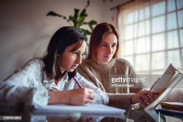 mother and adolescent child studying together. - mexican mothers day stock photos and pictures