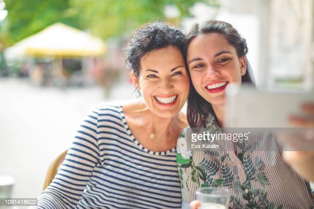 mother and adult daughter are taking selfies - só adultos imagens e fotografias de stock