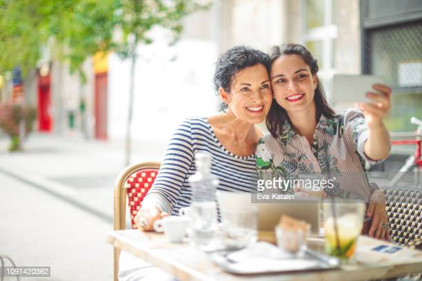 mother and adult daughter are taking selfies - mother's day stock pictures, royalty-free photos & images