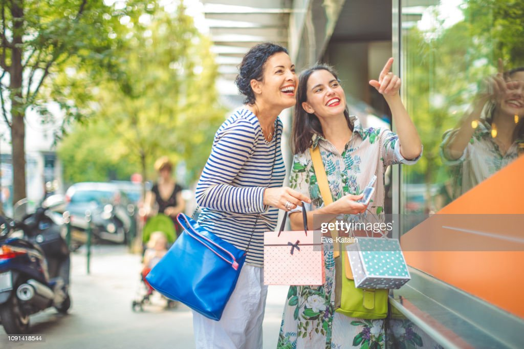 Mother and adult daughter are window shopping together : Stock Photo