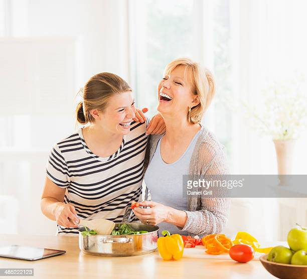 Mother and adult daughter cooking together