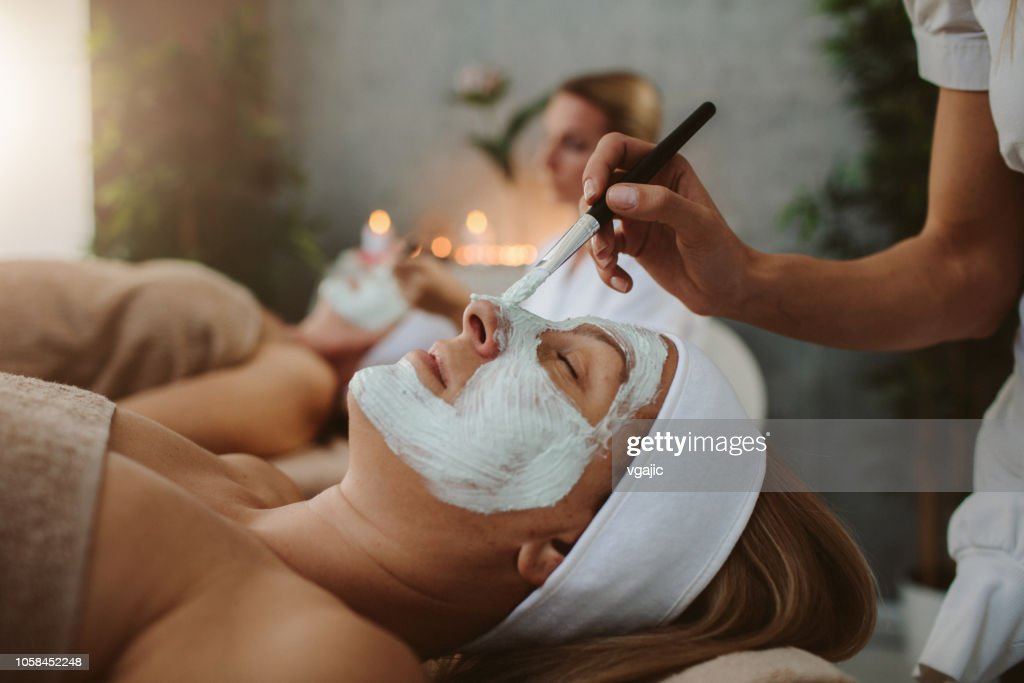 Mother and adult daughter enjoy beauty treatment in a spa center : Stock Photo