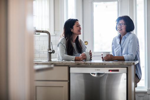 mother and adult daughter having coffee in kitchen - gettyimageskorea