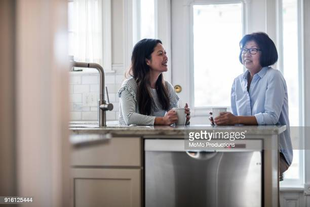 mother and adult daughter having coffee in kitchen - mother daughter stock photos and pictures