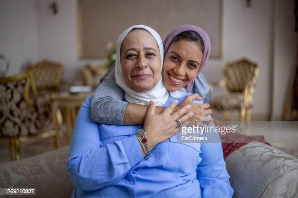 mother and adult daughter in the living room - islam stock pictures, royalty-free photos & images
