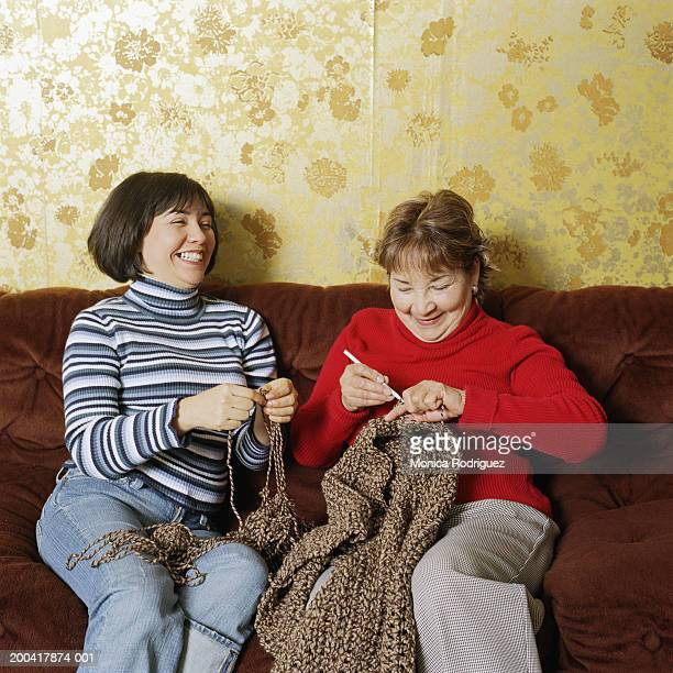 Mother and adult daughter knitting on sofa