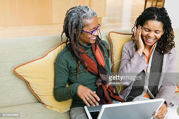 mother and adult daughter listening to mp3 - disruptaging stock pictures, royalty-free photos & images