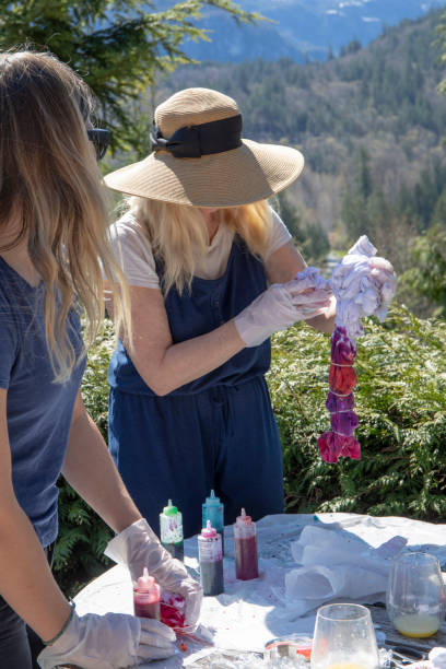 Mother and adult daughter make tie dye shirts outside