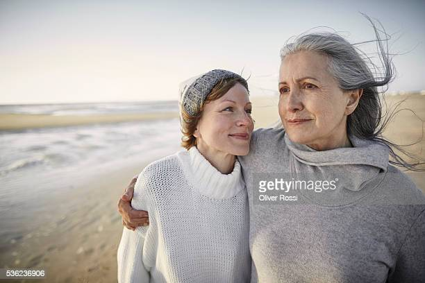 mother and adult daughter on beach - nur erwachsene stock-fotos und bilder