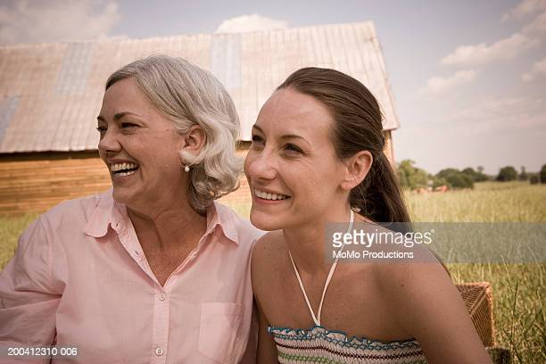 Mother and adult daughter, outdoors, smiling
