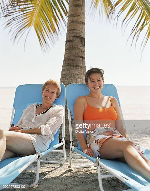 Mother and adult daughter relaxing on sun loungers on beach, portrait