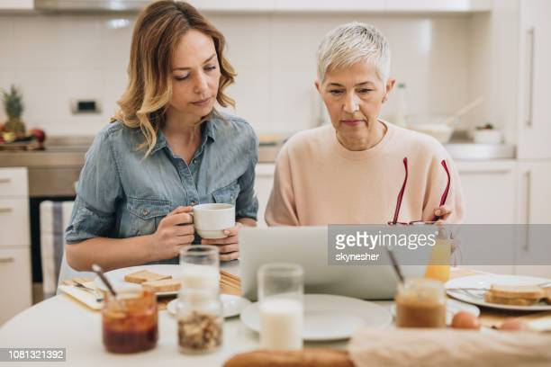 Mother and adult daughter surfing the Internet on laptop at dining room.