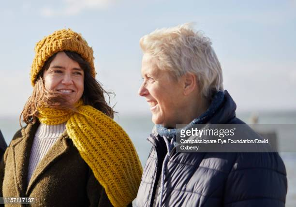 mother and adult daughter walking by sea - mid adult women stock pictures, royalty-free photos & images