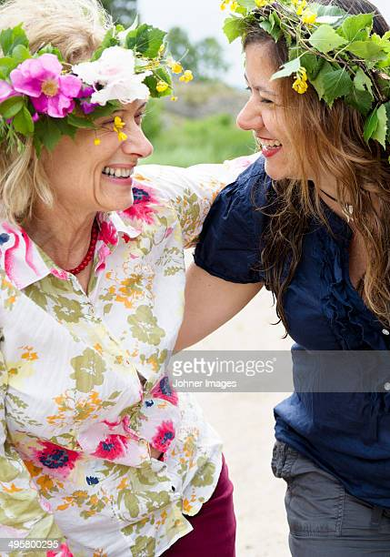 Mother and adult daughter wearing flower wreaths, Nykoping, Sodermanland, Sweden