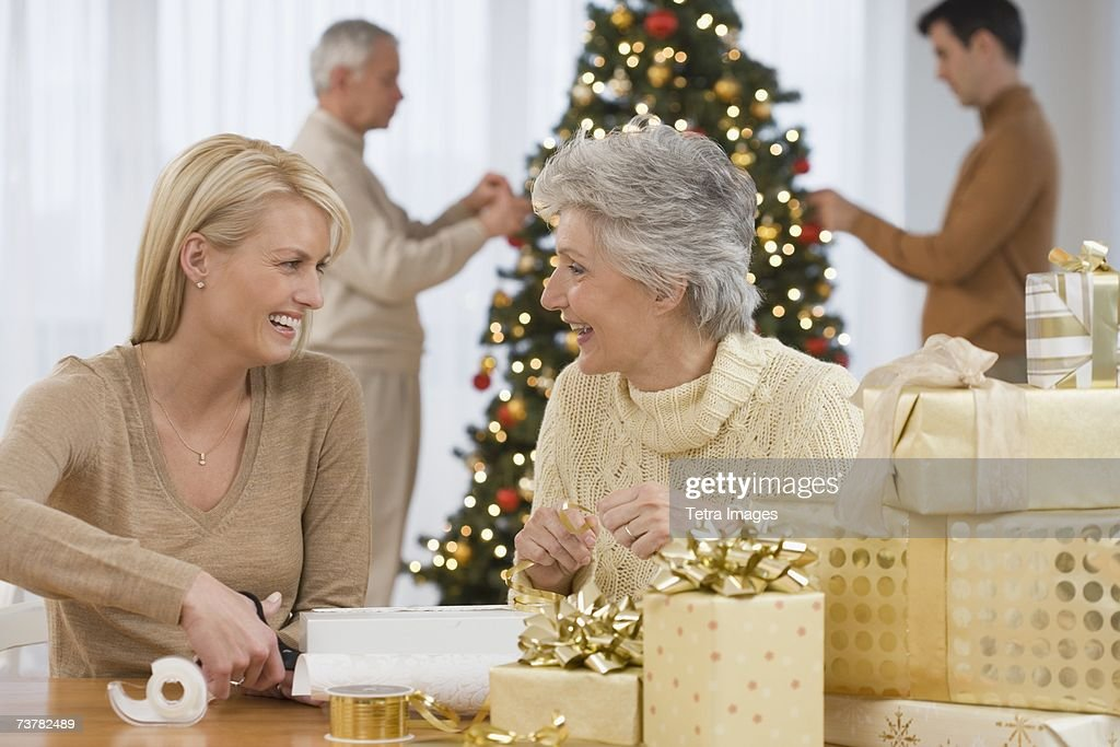 Mother and adult daughter wrapping Christmas gifts : Stock Photo