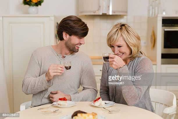 mother and adult son drinking espresso in the kitchen and having fun together - mom sits on sons lap stock pictures, royalty-free photos & images