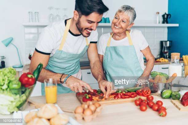 mother and adult son making salad together - festa della mamma foto e immagini stock