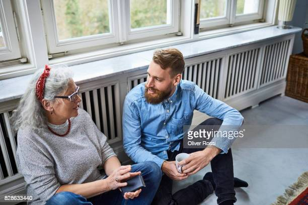 Mother and adult son talking at home