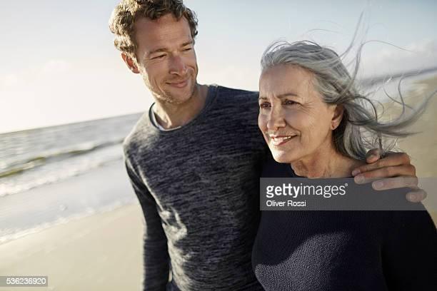 mother and adult son walking on beach - sohn stock-fotos und bilder