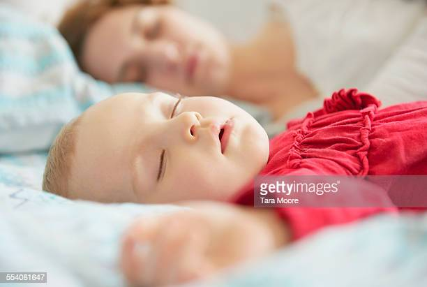 mother and baby asleep on bed - vida de bebé fotografías e imágenes de stock