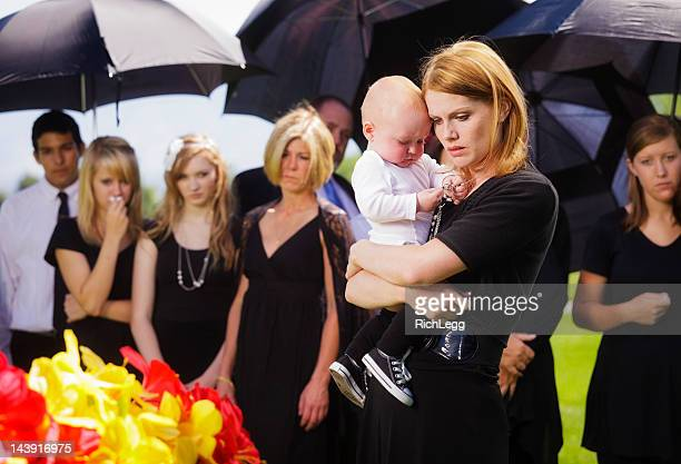 mother and baby at a funeral - funeral procession stock photos and pictures