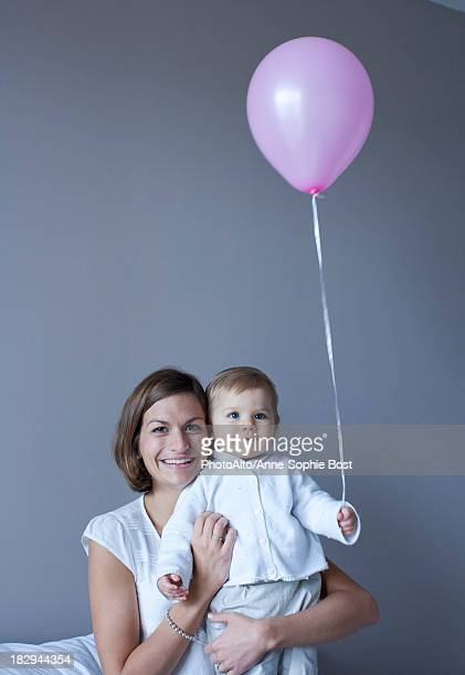 Mother and baby, baby holding balloon