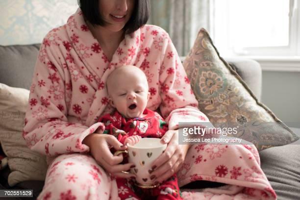 Mother and baby boy holding mug, sitting on sofa