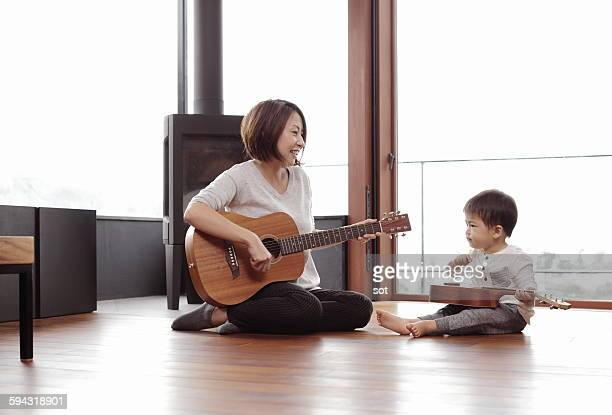 Mother and baby boy playing guitar and ukulele