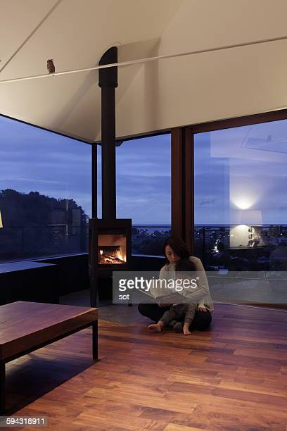 Mother and baby boy reading book by fireplace