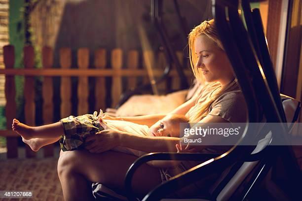 Mutter und baby boy entspannende zusammen auf einer Verandaschaukel.