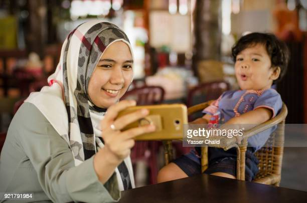 mother and baby boy selfie - 宗教的なベール ストックフォトと画像