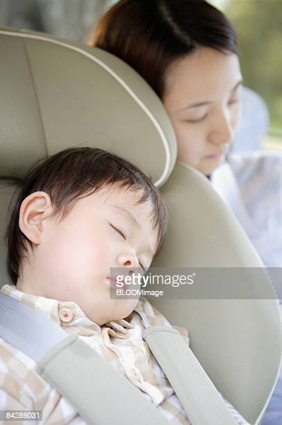 Mother and baby boy sleeping in car