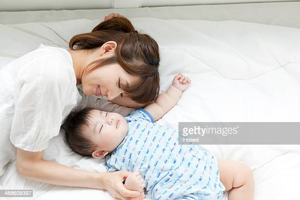 Mother and baby boy sleeping together in bed