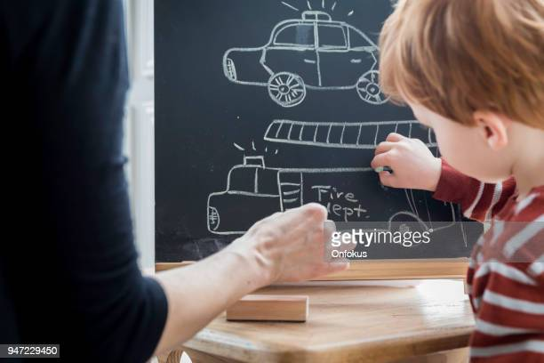Mother and Baby Boy Writing and Drawing on Black Board