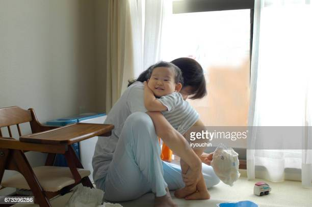 mother and baby changing diaper - diaper boy stock photos and pictures