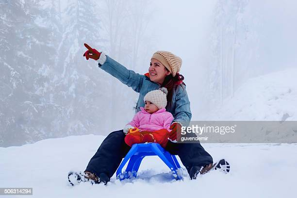Mother and baby daughter enjoying sledge