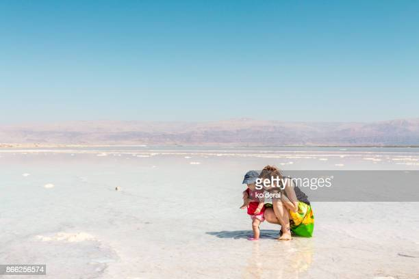 Mother and baby daughter in the shallow water of Dead Sea