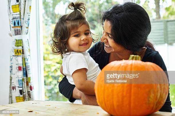 Mother and Baby Daughter looking at Carved Pumpkin