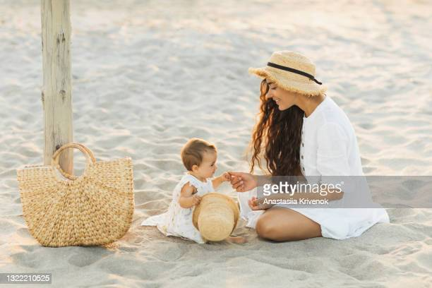 mother and baby daughter looking at each other, sitting on the sand, relaxing on the beach - peettante stockfoto's en -beelden