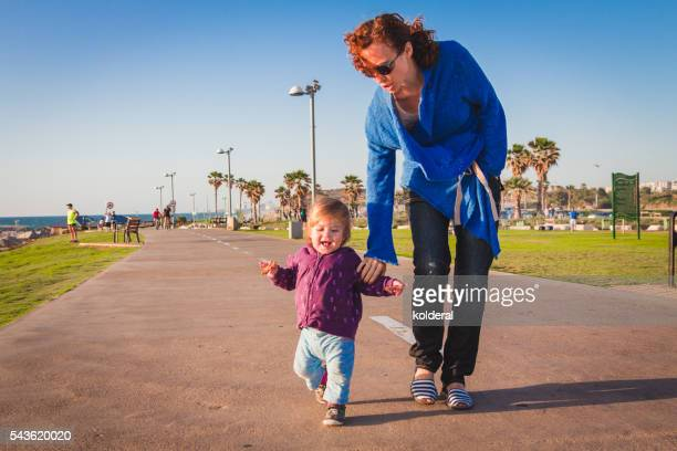 Mother and baby daughter on Mediterranean promenade