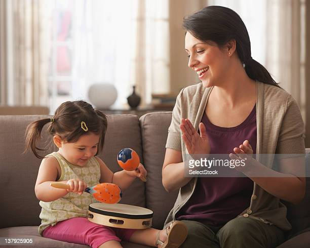 Mother and baby daughter playing with instruments