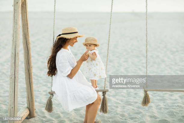 mother and baby daughter swinging on a big beautiful wooden swing on the beach - peettante stockfoto's en -beelden