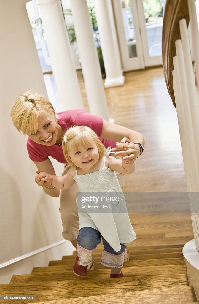 mother and baby daughter (9-12 months) walking up staircase : Foto stock