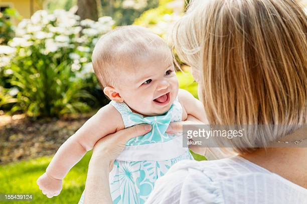 Mother and baby daugther outdoors playing