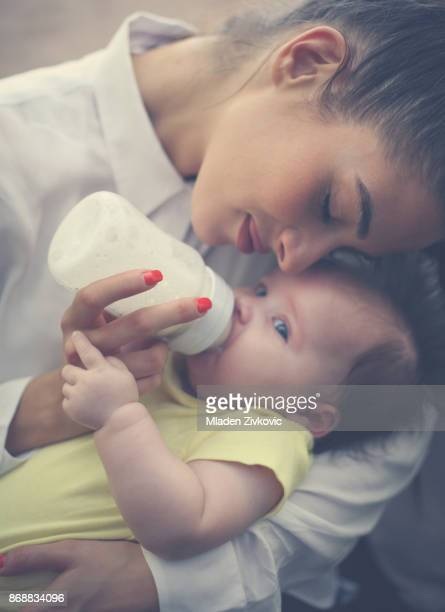 Mother and baby girl at home. Mother feeding her little baby. Close up.